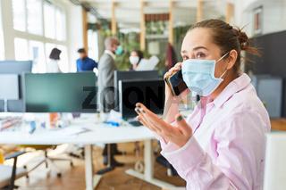 Geschäftsfrau mit Mund-Nasen-Schutz telefoniert mit Handy