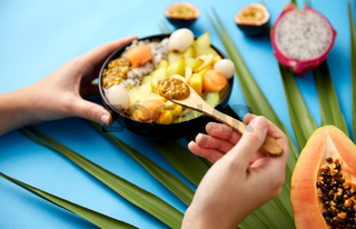 hands with mix of exotic fruits and wooden spoon