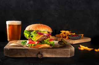 Burger and beer. Hamburger with beef, cheese, onion, tomato, and green salad, with pickles and French fries, a side view on a black background