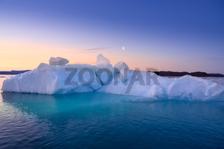 floating glaciers in the rays of the setting sun at polar night with Moon