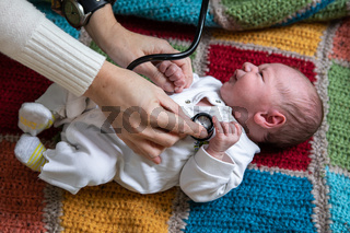 Woman checking baby using stethoscope