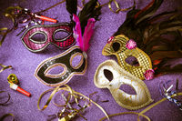 Assortment of Venetian carnival masks on violet background. Concept of mardi gras mask or disguise