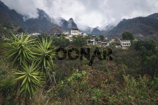 View up to steep mountains with palm trees with the village of Santa Cruz la Laguna, Guatemala