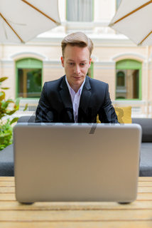 Young handsome blond businessman using laptop at the coffee shop
