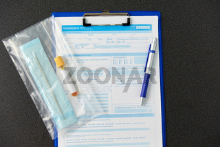 beaker with test, cotton swab and medical report