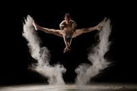 Male gymnast jumping in dust cloud view
