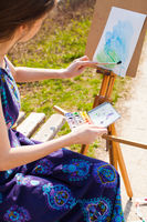 Girl is painting with watercolor on the easel outdoors. Spring imagination.