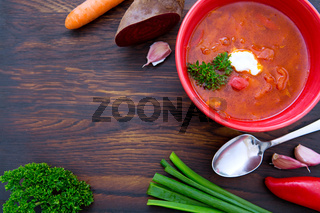 Red borscht soup with parsley in brown bowl on wooden.