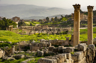 General view of the historical Roman site Gerasa in Jerash, Jordan, with pillars and Oval Plaza. Mountains and city in the far distance