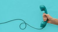 A vintage dial telephone handset with one hand and background.