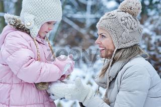 Kind baut mit Mutter Schneemann im Winter