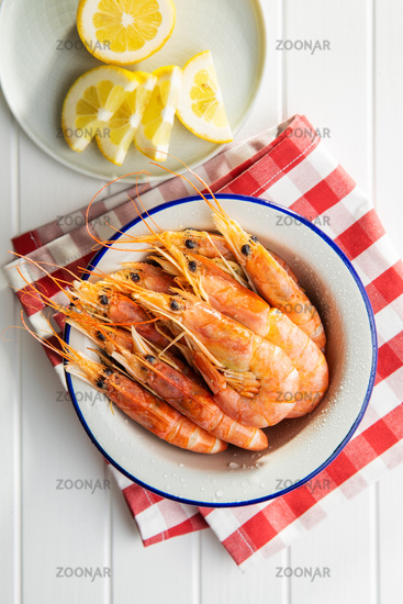 Boiled tiger prawns in bowl on white table.