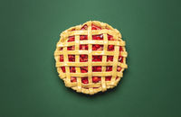 Uncooked strawberries rhubarb pie top view on a green background