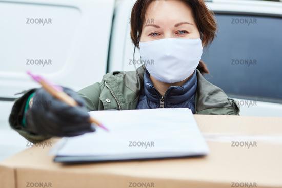Paketbotin mit Mundschutz bittet um Annahme Unterschrift