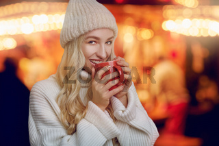 Young woman enjoying a mug of hot coffee