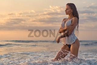 Sexy woman posing on beach near the sea at sunrise