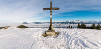 Summit Cross on snow mountain with blue Sky and great view to Mountain Range above valley fog layer. Backpack and Hiking Poles. Rangiswanger Horn, Alps, Allgau, Bavaria, Germany.