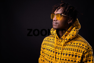 Young African man with dreadlocks against black background