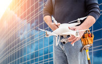 Construction Worker and Drone Pilot With Toolbelt Holding Drone At City High-Rise Building