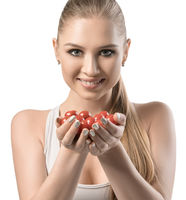 View of a beautiful young woman holding tomatoes