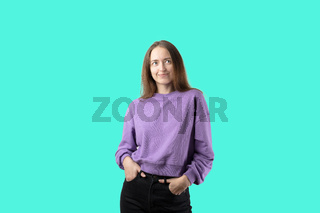 young caucasian woman on turquoise background in purple sweater. Happy millennial girl