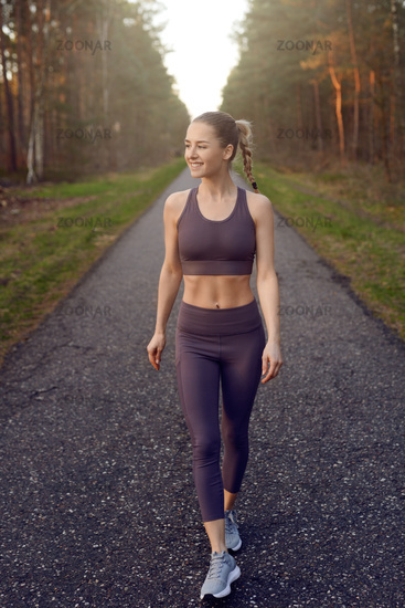 Fit healthy young woman walking on a forest track