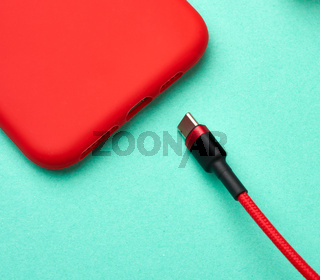 red smartphone and cable in textile braid on a green background