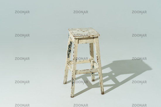 Tall retro stool or tabouret with peeling white paint on white background. Empty place