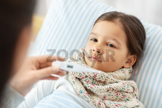 mother measuring temperature of sick daughter