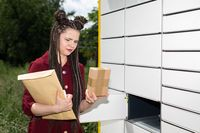 A teenager takes a parcel out of a parcel locker. Open mailbox. The girl pulls all the parcels from the letterbox.