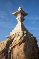 Stone lantern on boulder near Take Island in Gamagori, Japan.