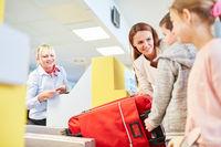 Familie mit Kindern bei Gepäckaufgabe im Flughafen