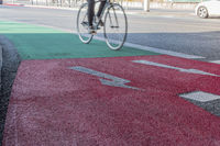 Bicycle path with a transition from green to red with a cyclist