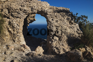 Natural stone arch with view to the ocean on a cliff of the natural park 'Serra Gelada' in Albir, Spain
