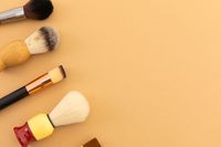 High angle view of selection of makeup and shaving brushes on yellow background