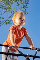 Little boy sitting on ropes in a playground