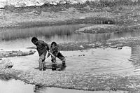 Mongolian boys fishing in the shallow water of the Tuul river in Ulaanbaatar, Mongolia, 1977
