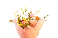 A delicate bouquet of different flowers in a light pink wrapper stands on a light background in a home setting.