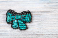 bow tie brooch from glass green bugles on gray