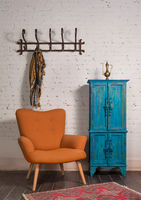French orange wingback armchair, vintage cupboard, and wall hanger with ornate scarf on bricks wall