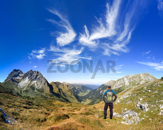Hiker Man with Backpack enjoying great clear view in the mountain with beautiful clouds. Alps, Kleinwalsertal, Gemsteltal, Austria.