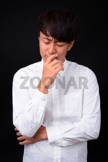 Young handsome Asian businessman against black background