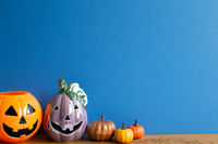 Halloween pumpkins on table with blue copy space