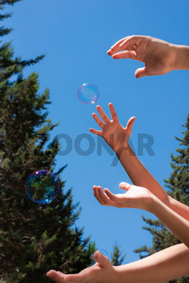 Soap bubbles in children hands against a blue sky
