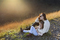Young mother and her little daughter outdoors on sunny autumn day