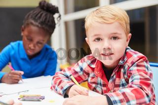 Junge malt im Kindergarten mit Wachsmalstift