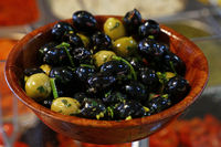 Black olives in wooden bowl on retail display