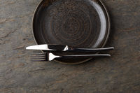Plate, knife and fork on stone background
