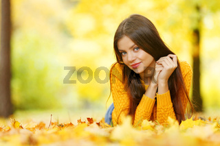 Girl laying on autumn leafs