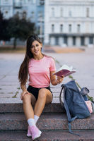 Cheerful young woman taking notes while sitting on steps otdoors